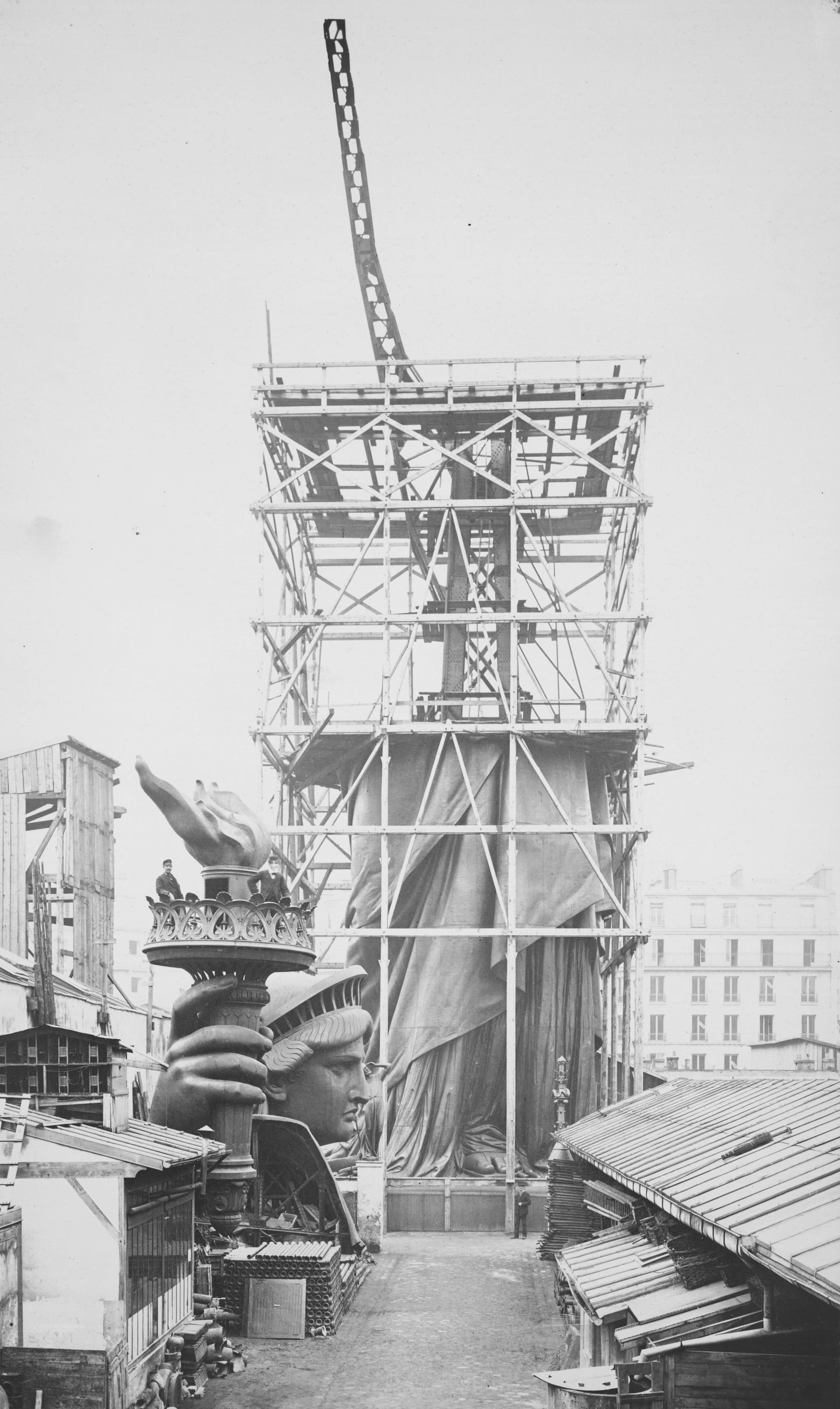 Albert Fernique, _Assemblage of the Statue of Liberty in Paris, Showing the Bottom Half of the Statue Erect under Scaffolding, the Head and Torch at Its Feet,_ 1883. © The Miriam and Ira D. Wallach Division of Art, Prints and Photographs: Photography Collection, The New York Public Library, Public Library Digital Collection